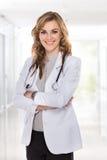 Женский доктор стоя с ее пересеченными оружиями и усмехаться Стоковое фото RF