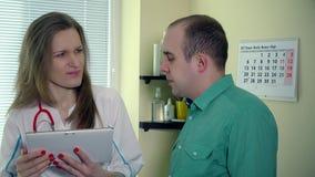 Женский доктор с планшетом говорит плохой диагноз для мужского терпеливого человека акции видеоматериалы
