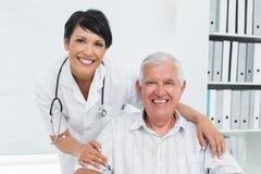 Женский доктор с счастливым старшим пациентом Стоковые Изображения