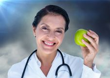 Женский доктор с яблоком против облаков и пирофакелов Стоковые Фотографии RF