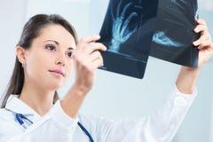 Женский доктор examing рентгеновский снимок Стоковые Фото