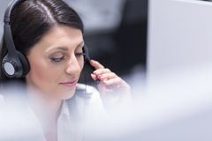 Женский оператор центра телефонного обслуживания делая ее работу стоковое фото