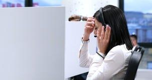 Женский оператор центра телефонного обслуживания делая ее работу Стоковые Изображения