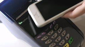 Женский оплачивать через умный телефон используя технологию NFC Конец-вверх 4K Девушка делает приобретение с банком или кредитной видеоматериал