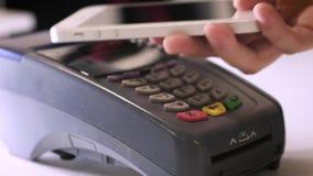 Женский оплачивать через умный телефон используя технологию NFC Конец-вверх 4K Девушка делает приобретение с банком или кредитной сток-видео