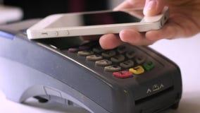 Женский оплачивать через умный телефон используя технологию NFC Конец-вверх 4K Девушка делает приобретение с банком или кредитной акции видеоматериалы