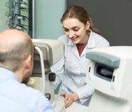 Женский офтальмолог и зрелый пациент проверяя зрение в c Стоковое Фото