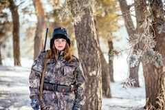Женский охотник в камуфлировании одевает готовое для того чтобы поохотиться, держащ оружие a стоковая фотография rf
