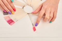 Женский палец выбирая цвет ногтя Стоковые Изображения RF