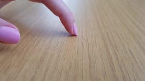 Женский палец с белой кожей и розовым коротким ногтем царапая деревянный стол сток-видео