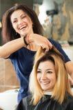 Женский парикмахер и клиент решая какую стрижку для того чтобы сделать Стоковые Изображения RF