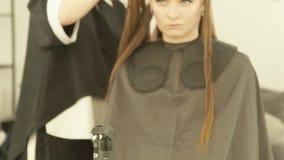 Женский парикмахер расчесывая и разделяя волосы во время парикмахерских услуг в салоне красоты Закройте вверх по haircutter испра сток-видео