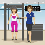 Женский пассажир женщины скеннирования охранника на контрольно-пропускном пункте с металлоискателем в авиапорте Стоковые Изображения