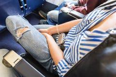 Женский пассажир при прикрепленный ремень безопасности пока сидящ на самолете для безопасного полета Стоковые Фото