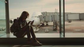 Женский пассажир сидит на windowsill в крупном аэропорте, использует smartphone Против фона огромного стоковое фото