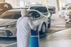 Женский пассажир с большой прогулкой багажа ролика для ожидания автомобиля скомплектовать вверх стоковое фото