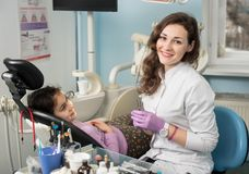Женский пациент дантиста и девушки после обрабатывать зубы на зубоврачебном офисе клиники стоковые фотографии rf