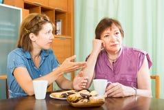 Женский пенсионер имея переговор с ее дочерью стоковые изображения