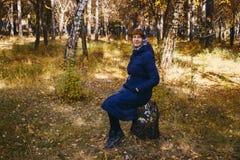 Женский пенсионный возраст сидя на пне дерева в лесе стоковые фотографии rf