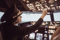 Женский пилотный капитан подготавливает для самолета взлета стоковые изображения