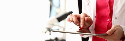 Женский ПК планшета владением руки доктора против стоковые фото