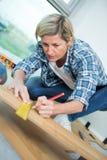 Женский плотник измеряя соответствующую деревянную доску в мастерской Стоковая Фотография