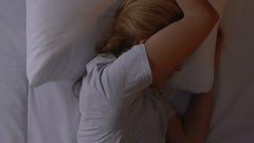 Женский поворачивать в заволакивание кровати с одеялом, страдая от разлада инсомнии сток-видео