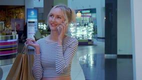 Женский покупатель говорит на телефоне на моле стоковое фото
