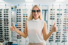 Женский покупатель пробует дальше солнечные очки в магазине оптики стоковые фото