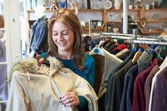 Женский покупатель в магазине хозяйственности смотря одежды Стоковое Фото