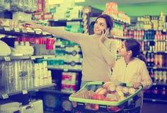 Женский покупатель говоря на телефоне быть с подростком Стоковая Фотография