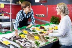 Женский покупать пенсионера охлаженный на рыбах льда стоковые фото