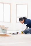 Женский построитель измеряя планку древесины стоковая фотография