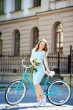 Женский представлять с пионами приближает к винтажному велосипеду смотря камеру Стоковая Фотография RF