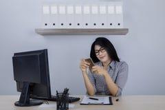 Женский предприниматель используя телефон около компьютера Стоковые Изображения RF