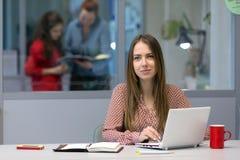 Женский предприниматель сидя на таблице офиса с компьютером Стоковая Фотография