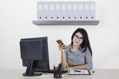 Женский предприниматель с мобильным телефоном в офисе Стоковые Изображения RF