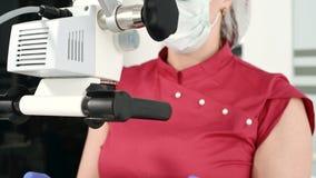Женский профессиональный дантист рассматривает женского пациента с stamotologic микроскопом в ее офисе Stamotologist видеоматериал