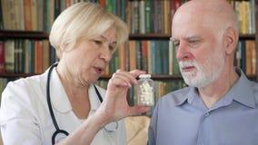 Женский профессиональный доктор на работе Старший врач советуя с больным пациентом дома о новых пилюльках видеоматериал