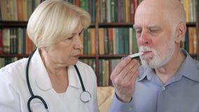 Женский профессиональный доктор на работе Температура старшего врача измеряя к пациенту термометром сток-видео