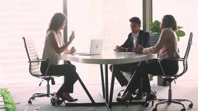 Женский профессиональный консультант по капиталовложениям советуя с разнообразным клиентом на деловой встрече акции видеоматериалы