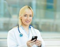Женский профессионал здравоохранения, доктор держа умный телефон стоковое фото rf