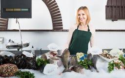 Женский продавец в магазине рыб Стоковые Фото