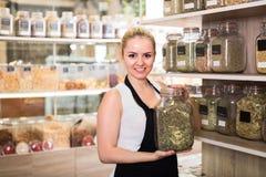 Женский продавец с опарником высушенных трав Стоковая Фотография