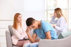 Женский психолог работая с подростком и его матерью в офисе Стоковые Фото