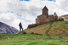 Женский путешественник на предпосылке церков троицы Gergeti или Tsminda Sameba около деревни Stepantsminda, Georgia стоковое изображение