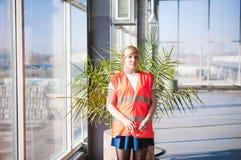 Женский работник в жилете оранжевой робы нося в комнате продукции рабочей зоны, против окон предпосылки больших весь путь от ceil Стоковое фото RF
