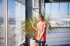 Женский работник в жилете оранжевой робы нося в комнате продукции рабочей зоны, против окон предпосылки больших весь путь от ceil Стоковая Фотография RF