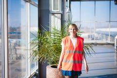 Женский работник в жилете оранжевой робы нося в комнате продукции рабочей зоны, против окон предпосылки больших весь путь от ceil Стоковое Изображение