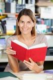 Женский работник держа красную книгу крышки в фабрике Стоковое Изображение